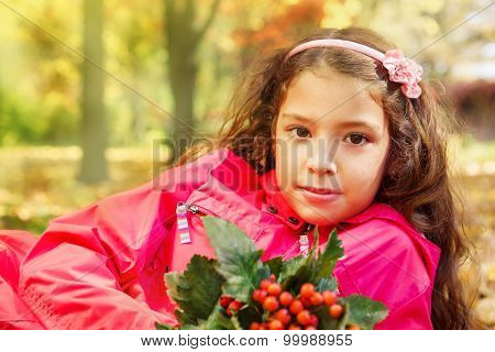 Portrait of a school girl holding bouquet of ripe ash berries, sitting in a yellow sunny park