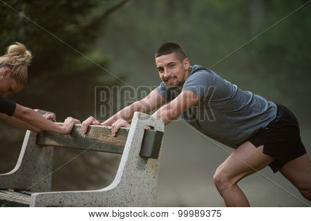 Young Couple Stretching Before Running In Wooded Forest
