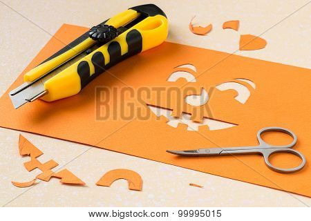 Cutting A Stencil Of Paper For Jack-o'-lantern