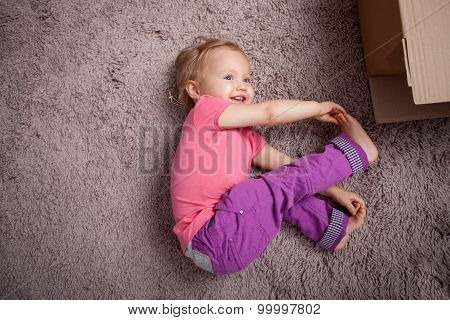 Pretty little child is making fun on floor