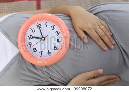Pregnant Women Show Clock On Her Belly To Tell The Time.