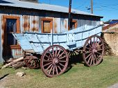 stock photo of ox wagon  - A real wagon from Pioneer days sits outside a blacksmith shop in downtown Grapevine - JPG