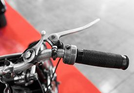 stock photo of levers  - vintage motorcycle with gear lever on the handlebar to operate with thumb and forefinger of the right hand - JPG
