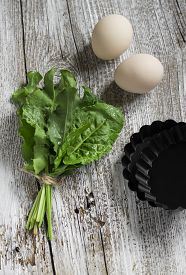 foto of sorrel  - fresh sorrel eggs and baking dish on a light wooden background ingredients for baked eggs with sorrel - JPG