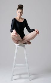image of leotard  - An attractive confident girl in black gymnastyc leotard is sitting on a high white chair - JPG